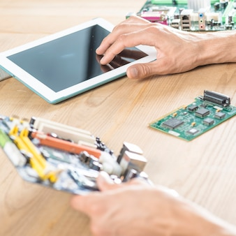 Male technician hand touching digital tablet holding motherboard on wooden table