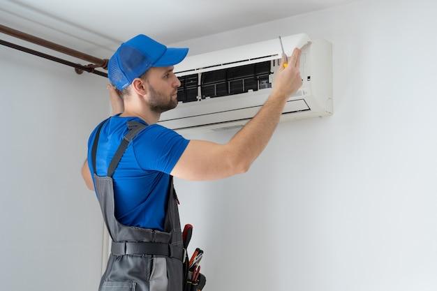 オーバーオールの男性技術者と青い帽子が壁のエアコンを修理します