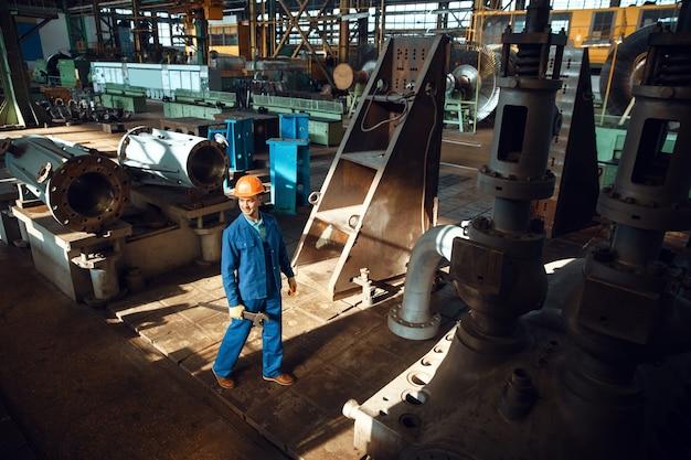 유니폼과 헬멧을 쓴 남성 기술자는 공장에 큰 렌치를 들고 있습니다. 산업 생산, 금속 공학, 동력 기계 제조