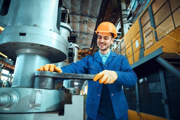 Мужской техник в униформе и шлеме работает на заводе