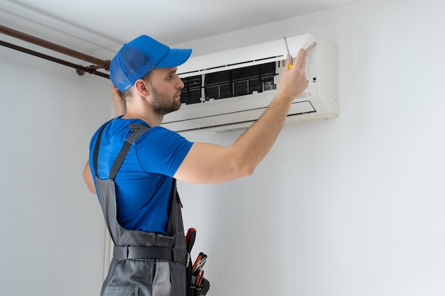 Male technician in overalls and a blue cap repairs an air conditioner on the wall