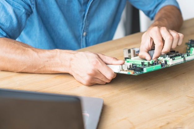 Male technician repairing motherboard at workbench