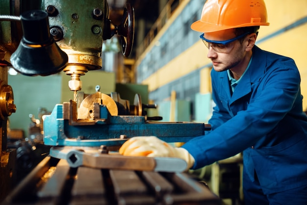 Male technician in uniform and helmet works on lathe, plant. industrial production, metalwork engineering, power machines manufacturing