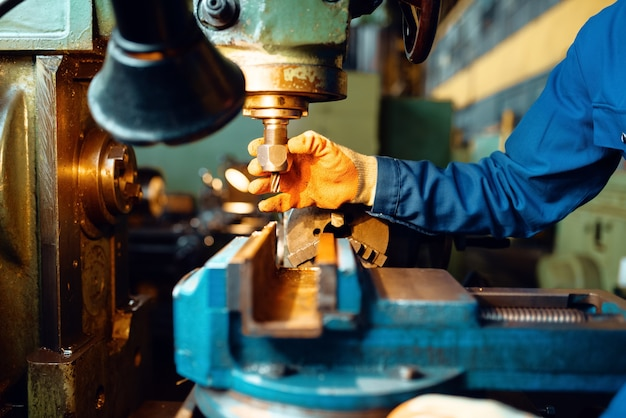 Male technician in uniform and helmet works on lathe, plant. industrial production, metalwork engineering