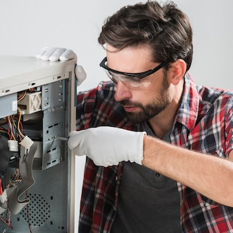 Male technician wearing safety glasses and gloves assembling computer cpu