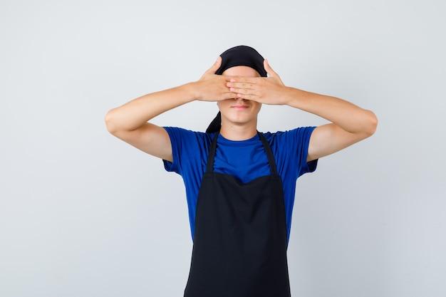 Повар-подросток мужского пола, закрывающий глаза руками в футболке, фартуке и пристыженный, вид спереди.
