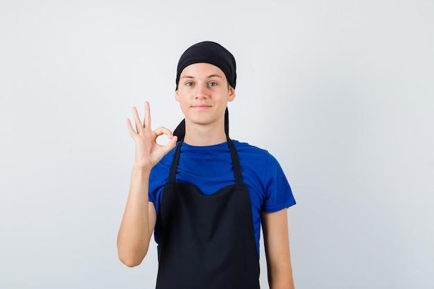 티셔츠를 입은 남성 10대 요리사, 앞치마는 확인 제스처를 보여주고 만족스러워 보입니다.