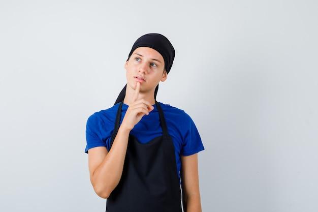 男性の10代の料理人は、tシャツ、エプロンであごに指を置き、夢中になっているように見えます。正面図。