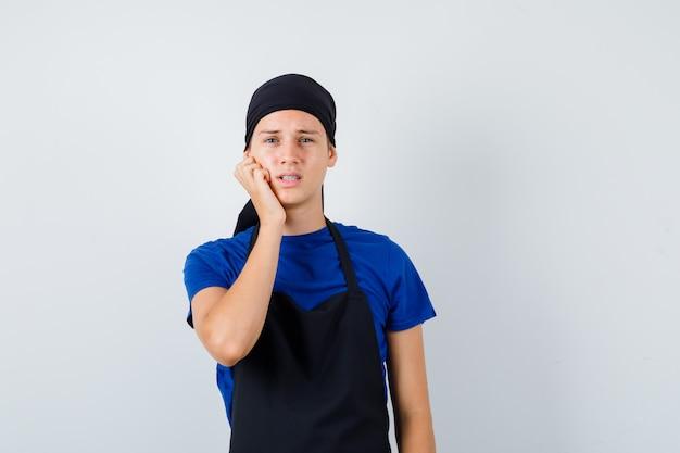Cuoco adolescente maschio che tiene la mano sulla guancia in maglietta, grembiule e sembra dispiaciuto. vista frontale.