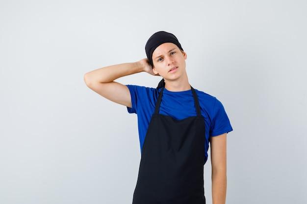 Cuoco adolescente maschio che tiene la mano dietro la testa in maglietta, grembiule e guarda pensieroso, vista frontale.