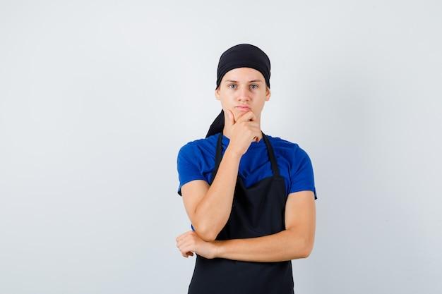 男性の10代の料理人は、tシャツ、エプロン、物思いにふけることであごに手を保ちます。正面図。