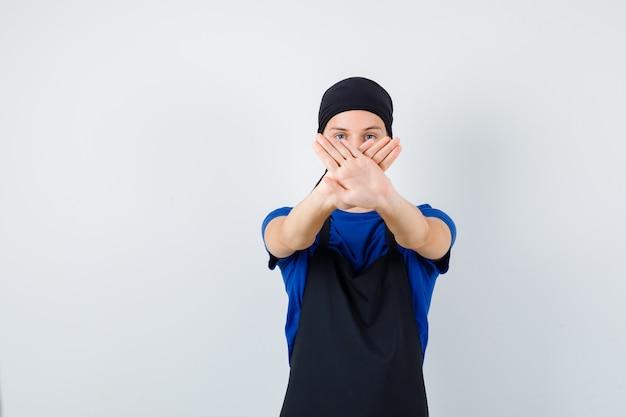 남성 10대 요리사는 티셔츠, 앞치마를 입고 거부하는 제스처를 보이고 짜증을 내며 정면을 바라보고 있습니다.