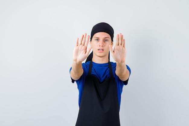Cuoco adolescente maschio che mostra gesto di rifiuto in maglietta, grembiule e sembra irritato, vista frontale.