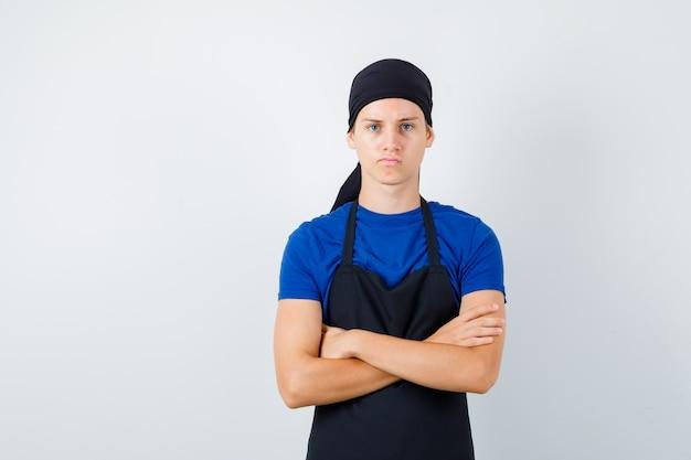 Cuoco adolescente maschio in t-shirt, grembiule con le mani incrociate e guardando scontento, vista frontale.