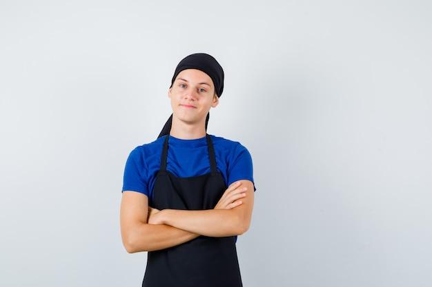 Cuoco adolescente maschio con le mani incrociate in maglietta, grembiule e guardando soddisfatto. vista frontale.
