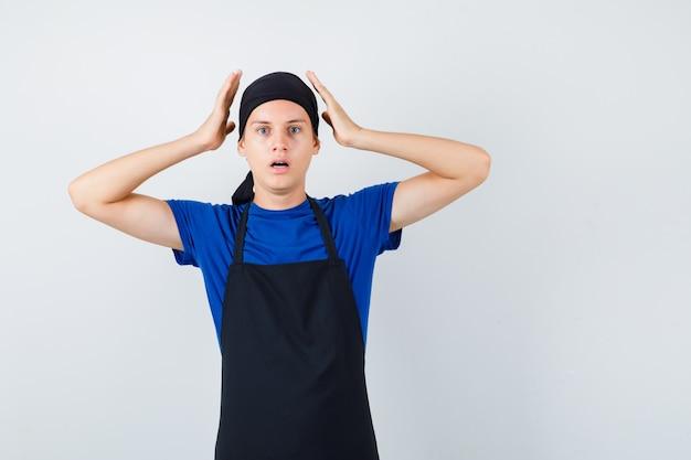 Мужчина-подросток готовит с руками возле головы, открывает рот в футболке, фартуке и выглядит испуганным, вид спереди.