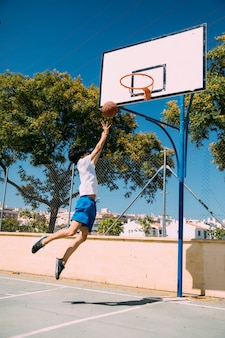 Male teen student making basketball jump shot