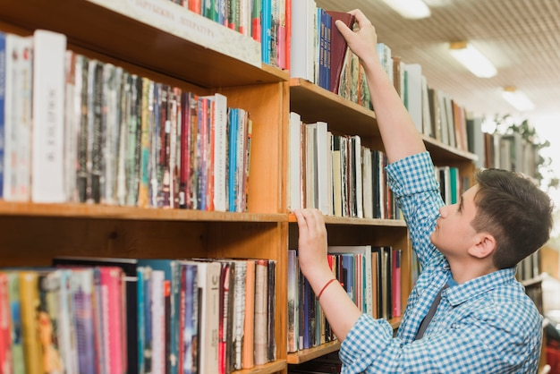 Male teenager picking book from bookshelf