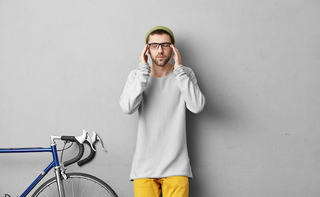 Male teenager wearing sweater and colorful trousers, trying to concentrate while standing in his room near his modern bicycle. attentive cyclist trying to solve all obstacles on his way