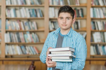 Male teenager with stack of books