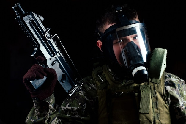검은 배경에 총을 들고 가스 마스크에 남성 테러리스트.