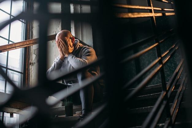 Мужской theif с бутылкой алкоголя сидит на лестнице