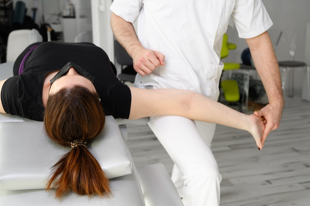 Male therapist giving massage to relief shoulder pain to a female patient in physiotheraphy clinic..