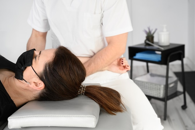 Male therapist giving massage to relief shoulder pain to a female patient in physiotheraphy clinic.
