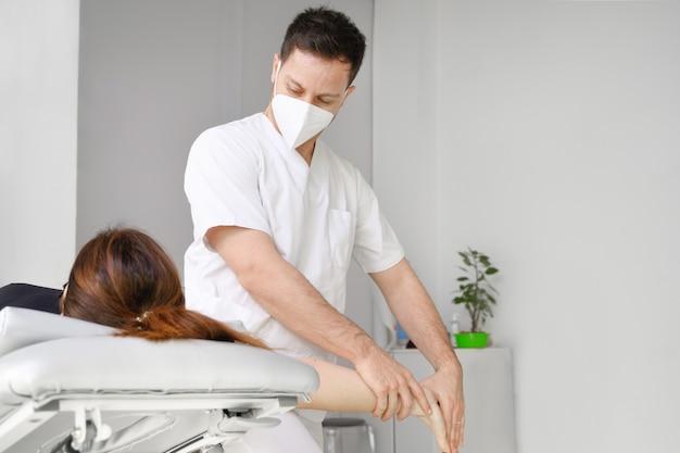 Терапевт-мужчина делает массаж для облегчения боли в плече пациентке в физиотерапевтической клинике.