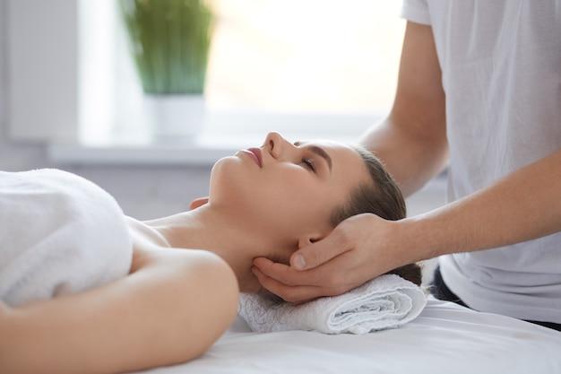 Мужчина-терапевт делает массаж головы клиентке.