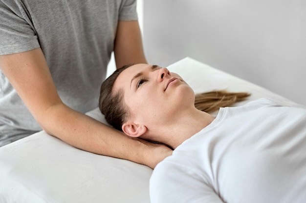 Male therapist undergoing physical therapy with female patient