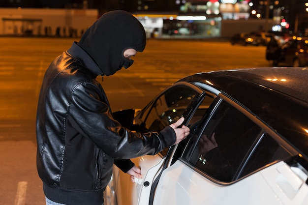 Male thief with balaclava on head opening car door