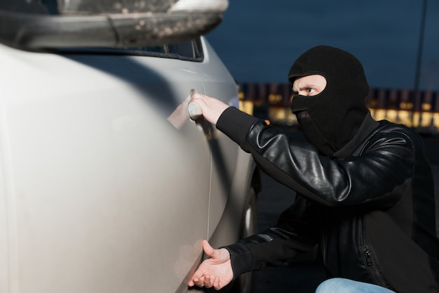 Male thief with balaclava on his head trying to open car door. carjacker unlock vehicle