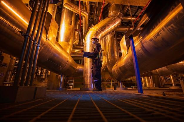 Мужчина, чтобы быть работником, визуальный осмотр внутри диспетчерской, резервуар с клапаном, трубопровод, электростанции