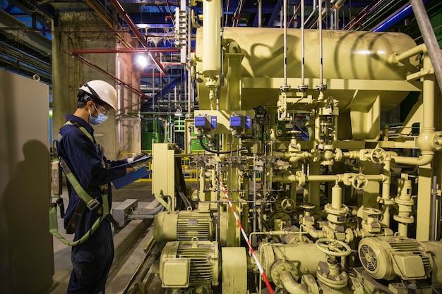制御室のバルブタンクパイプライン発電所内の労働者の目視検査となる男性