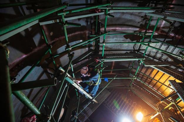 男性の上面図は、限られたスペース内の階段の足場検査タンクを登る