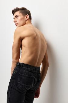Мужские топлес, стоя обратно в черные штаны, позируют роскошь моды.