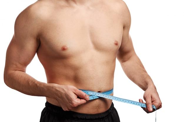 Male torso with measure tape on waistline
