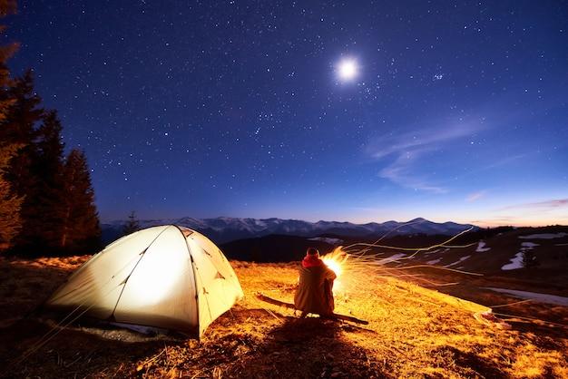 Мужчина турист отдыхает в своем лагере ночью у костра и в палатке под красивым ночным небом, полным звезд и луны и наслаждаясь ночной сценой в горах.