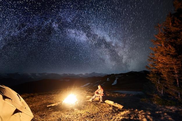 男性の観光客は星と天の川でいっぱいの美しい夜空の下で彼のキャンプで夜の残りを持っています。長期露出