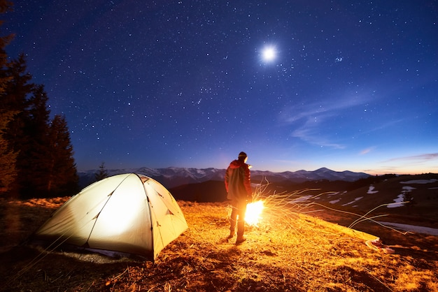 Male tourist have a rest in his camp at night, standing near campfire and tent under beautiful night sky full of stars and the moon and enjoying night scene in the mountains