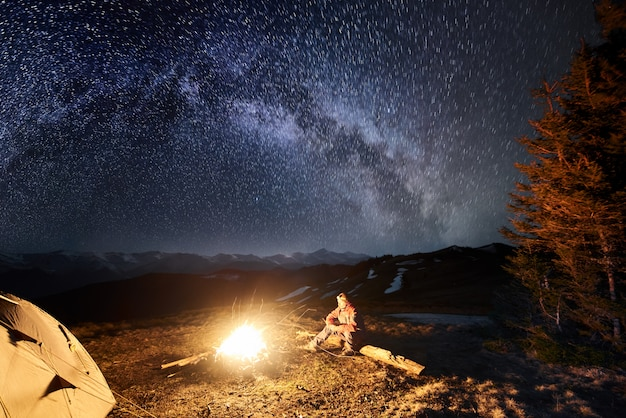 Male tourist have a rest in his camping at night under beautiful night sky full of stars and milky way. long exposure