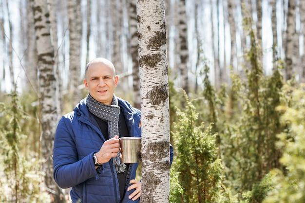 Мужской турист, держащий кружку в лесу
