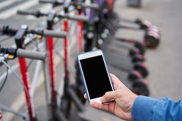 남성 관광객은 스마트 폰으로 전기 스쿠터 대여를 위해 앱 qr 코드를 사용하고 케이블 잠금을 해제 할 예정입니다.