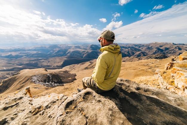 男性観光客は高山の背景に座っています