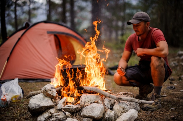Male tourist kindles bonfire in front of a tent