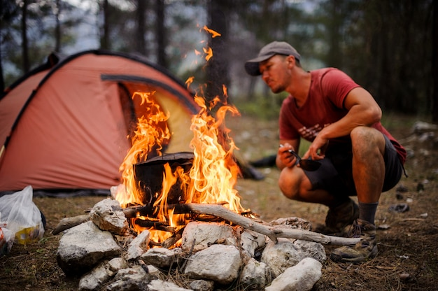 Male tourist kindles bonfire in front of the tent