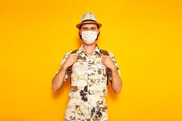 노란색 배경에 격리된 보호 의료 마스크에 배낭을 메고 휴가 중인 남성 관광객