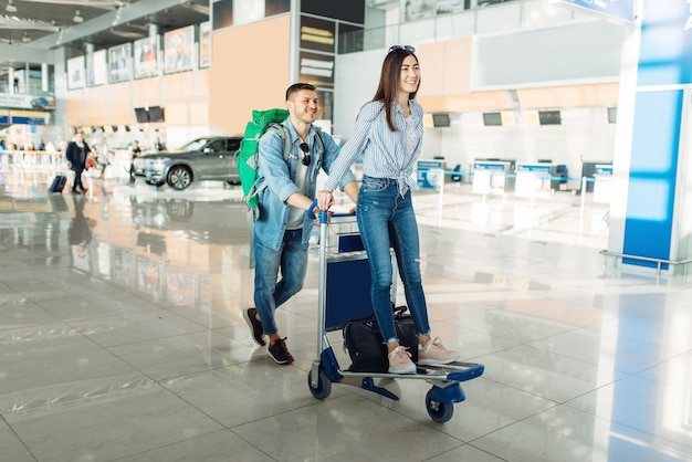 Male tourist roll the cart with luggage and his wife in airport.