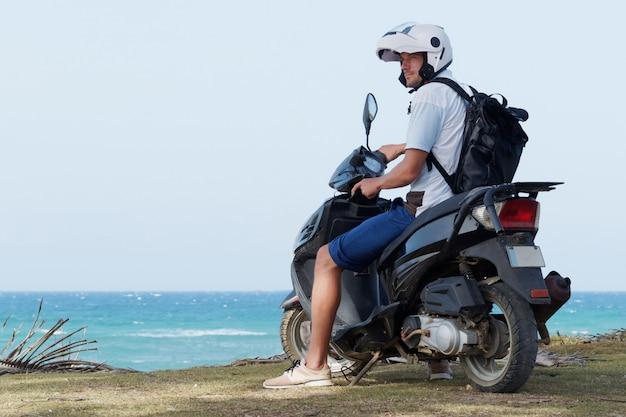Мужской турист, сидя на мотороллере на берегу океана.